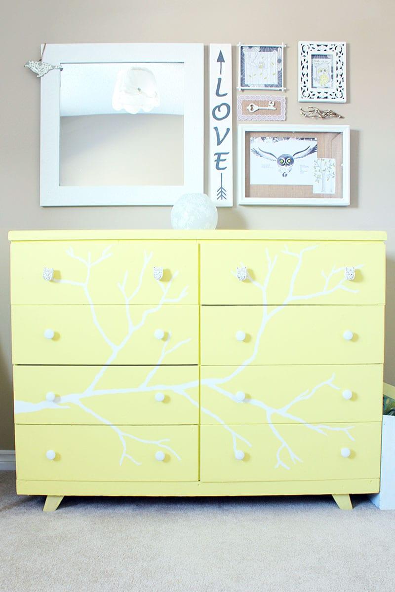 A yellow handpainted tree dresser.