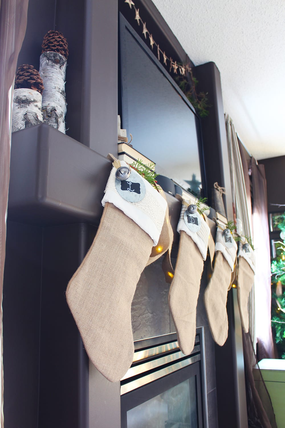 Nature inspired holiday decor featuring burlap stockings, fresh greenery, birch logs and pine cones.