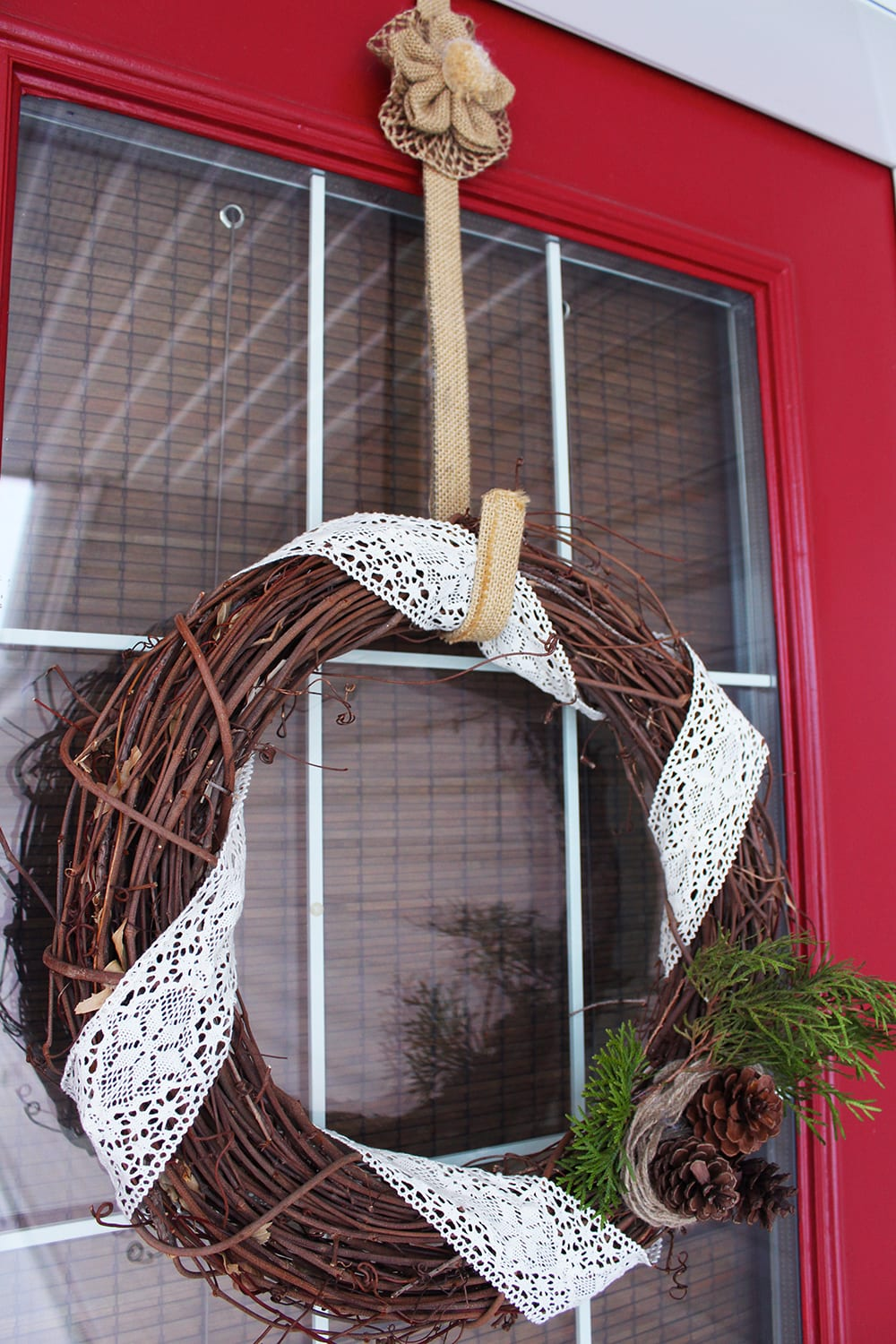 Nature inspired holiday decor featuring a grapevine wreath with lace, pine cones and fresh greenery - plus the bright red door adds an extra layer of Christmas-y cheer!