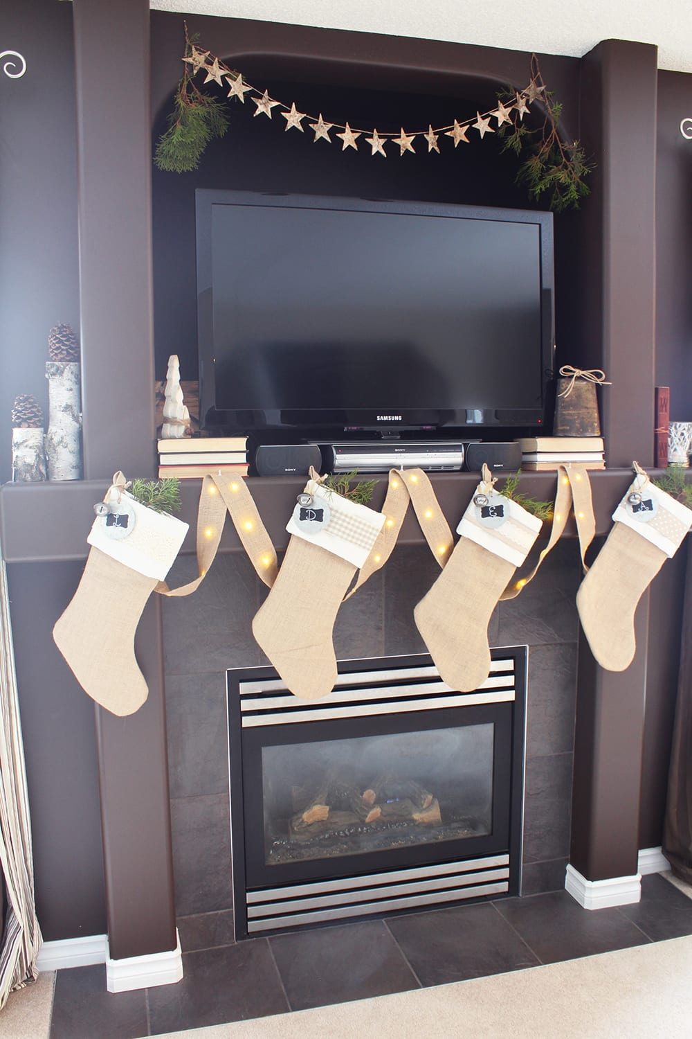 Nature inspired holiday decor featuring burlap stockings, birch logs, a star garland and fresh greenery.