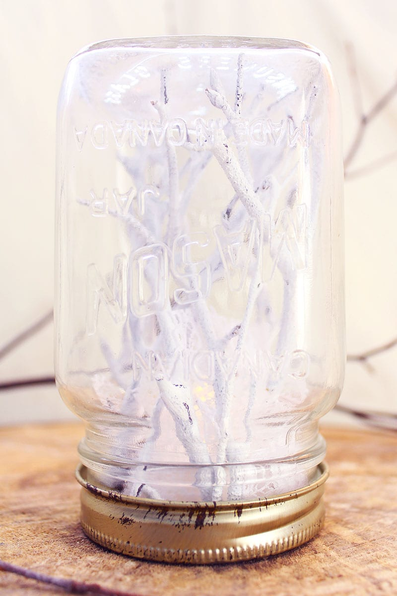 "Looking for winter craft ideas? How about foraged twigs for ""trees,"" pieces of lace for ""snow"" and a reused mason jar ""globe""? Kind of precious, right?"